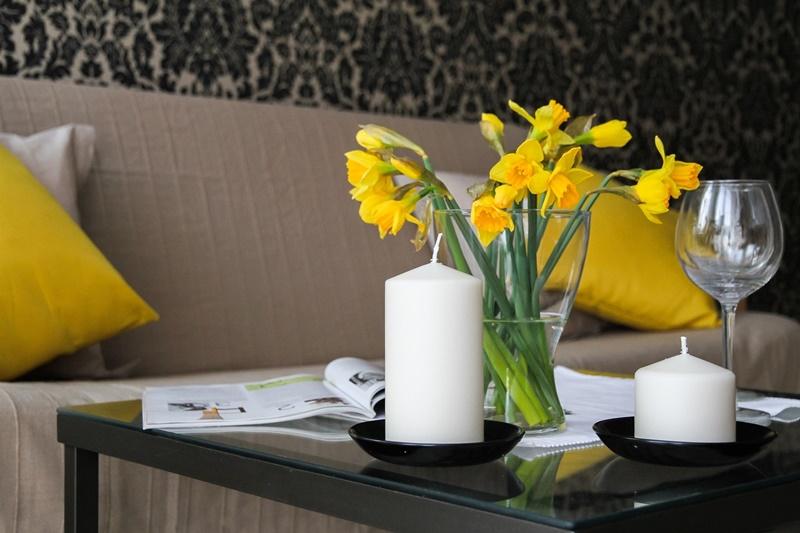Flor e uma vela encima da mesa